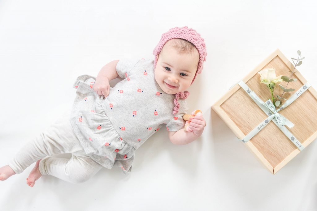 Baby in bonnet beside box website product photography