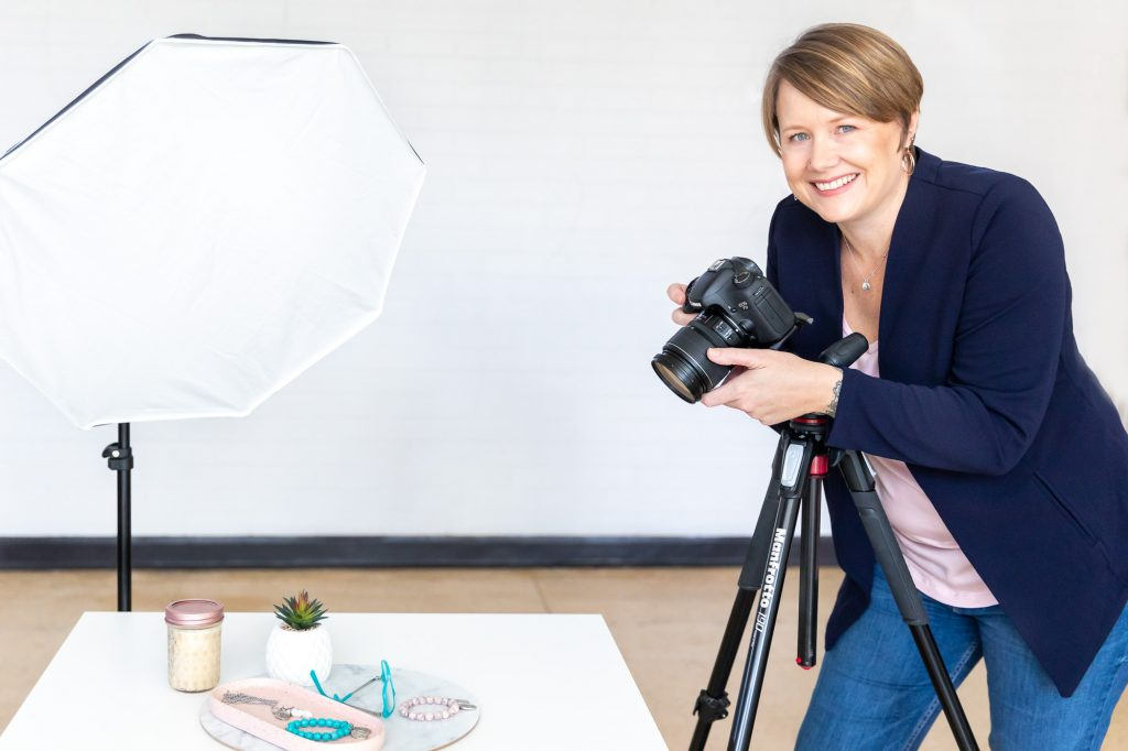 person wearing blue jacket and jeans taking a photo with light in the background