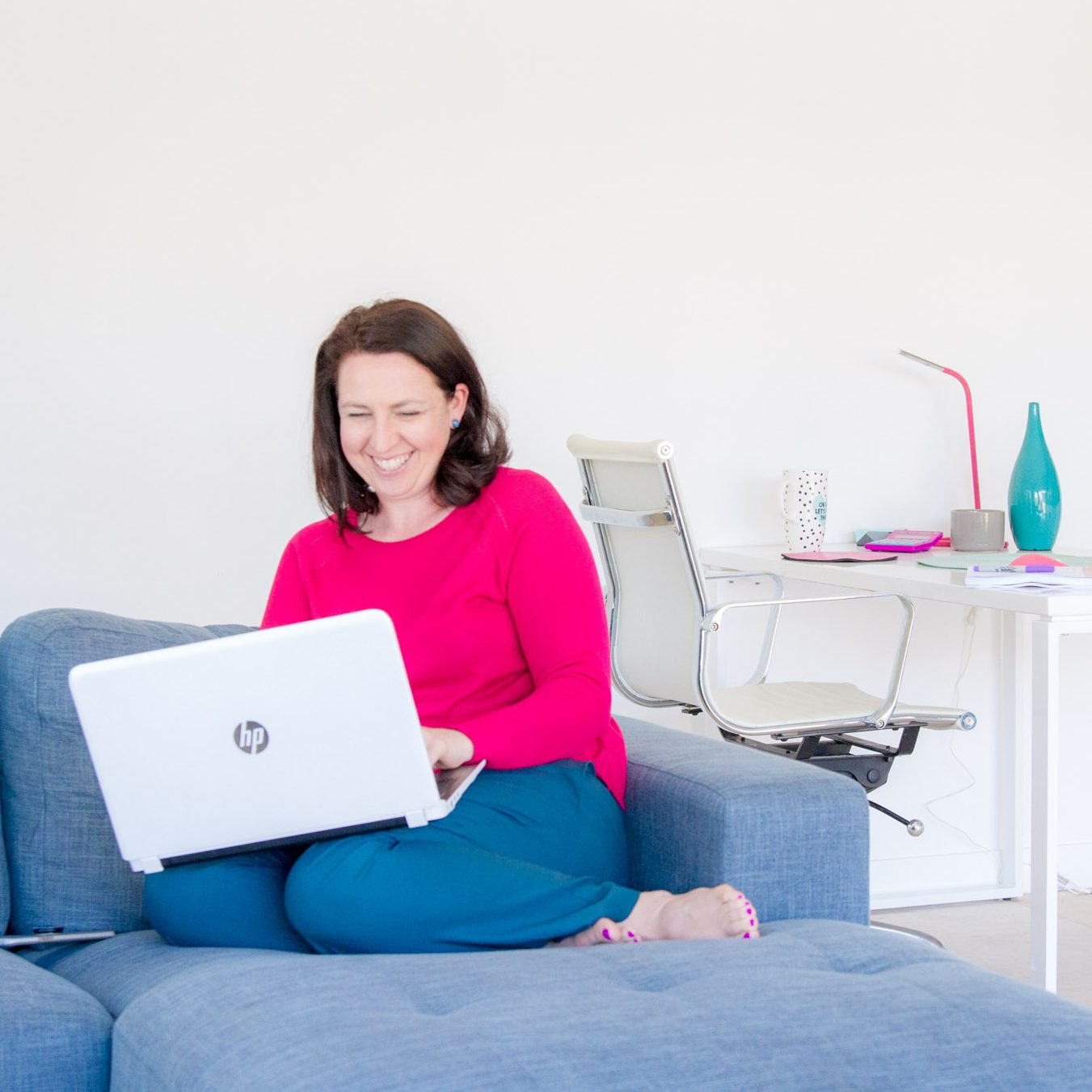 women in pink and blue on a blue couch with a white laptop