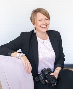AJ Harrington in a black suit and blush top sitting on a blush chair with a camera